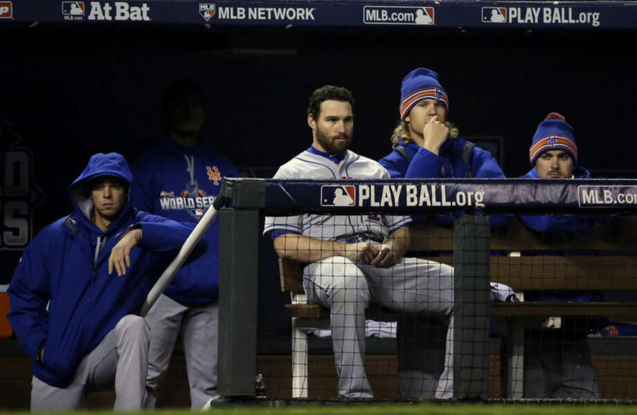 Some New York Mets watch from the dugout during the eighth inning of Game 2 of the Major League Baseball World Series against the Kansas City Royals Wednesday, Oct. 28, 2015, in Kansas City, Mo. (AP Photo/David J. Phillip)