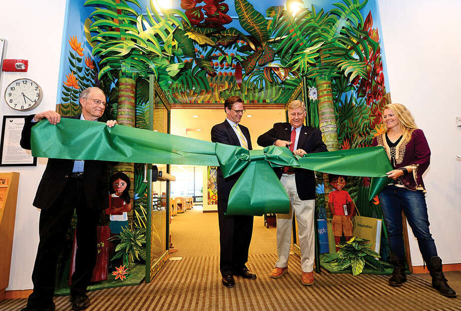 Artists Ed MacEwen and his daughter, Bonnie MacEwen Sailer, hold the ribbon as vice president of the Shoff Foundation, Doug Adams and president, Rich Mason, cut the ribbon during a ceremony at the Wilton Library for the newly decorated entrance to the Children's Library Thursday evening.