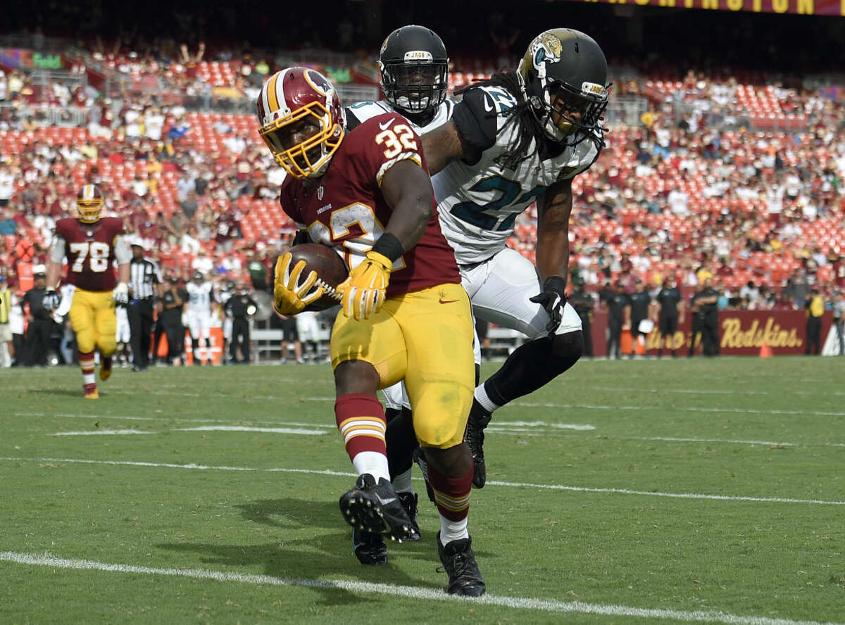 Washington Redskins running back Silas Redd (32) scores a touchdown in front of Jacksonville Jaguars free safety Winston Guy (22) and outside linebacker Telvin Smith (50) during the second half of an NFL football game Sunday, Sept. 14, 2014, in Landover, Md. The Redskins won 41-10. (AP Photo/Nick Wass)