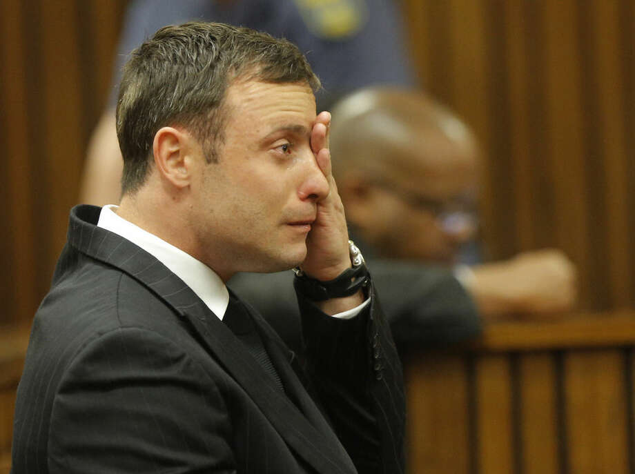 Oscar Pistorius cries in the dock in Pretoria, South Africa, Thursday, Sept. 11, 2014 as Judge Thokozile Masipa reads notes as she delivers her verdict in Pistorius' murder trial. The verdict is expected to take hours and possibly two days to present. She will decide with the help of two legal assessors if Pistorius is guilty of the murder of his girlfriend Reeva Steenkamp. (AP Photo/Kim Ludbrook, Pool)
