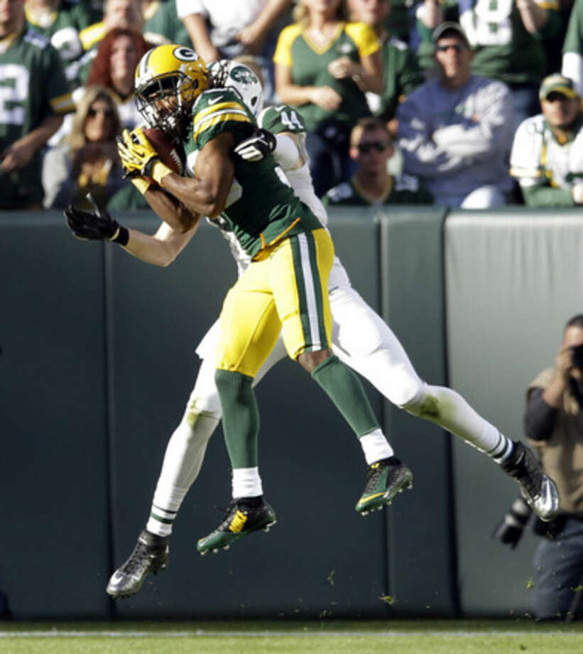Green Bay Packers' Tramon Williams intercepts a pass intended for New York Jets' Zach Sudfeld during the first half of an NFL football game Sunday, Sept. 14, 2014, in Green Bay, Wis. (AP Photo/Tom Lynn)
