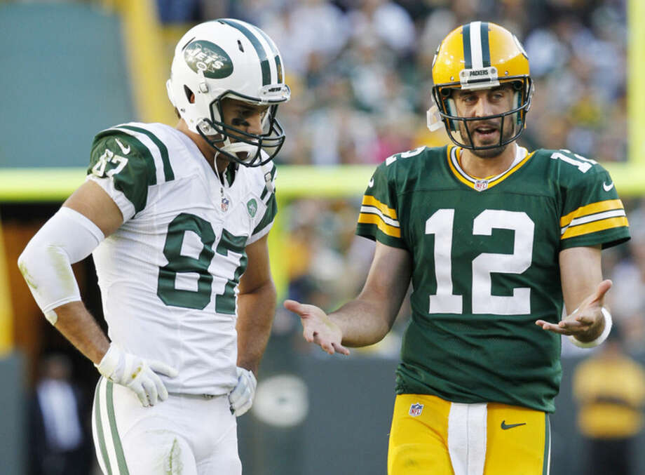 Green Bay Packers' Aaron Rodgers (12) talks to New York Jets' Eric Decker (87) during a review in the second half of an NFL football game Sunday, Sept. 14, 2014, in Green Bay, Wis. (AP Photo/Mike Roemer)