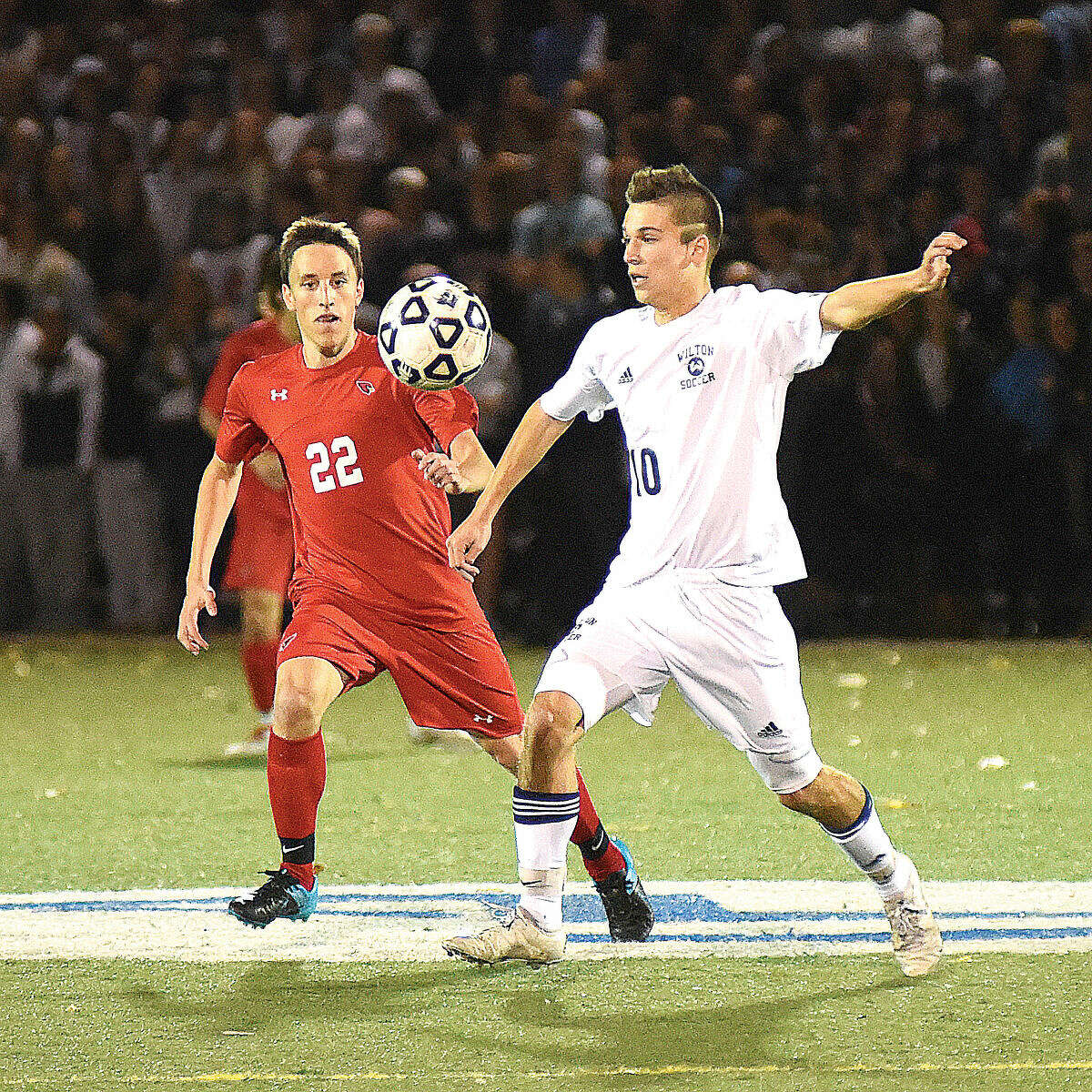 Hour photo/John Nash - Wilton's Jack Brandt, right, plays the ball past a Greenwich defender during Thursday's FCIAC boys soccer quarterfinal at Kristine Lilly Field in Wilton.