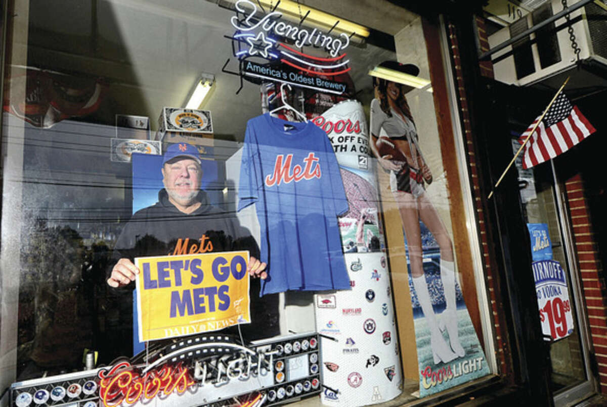Hour photo / Erik Trautmann Bob Macedo, owner of New Canaan Avenue Liquors in Norwalk, shows his allegiance to his favorite baseball team while standing in the window of his liquor store in Broad River.