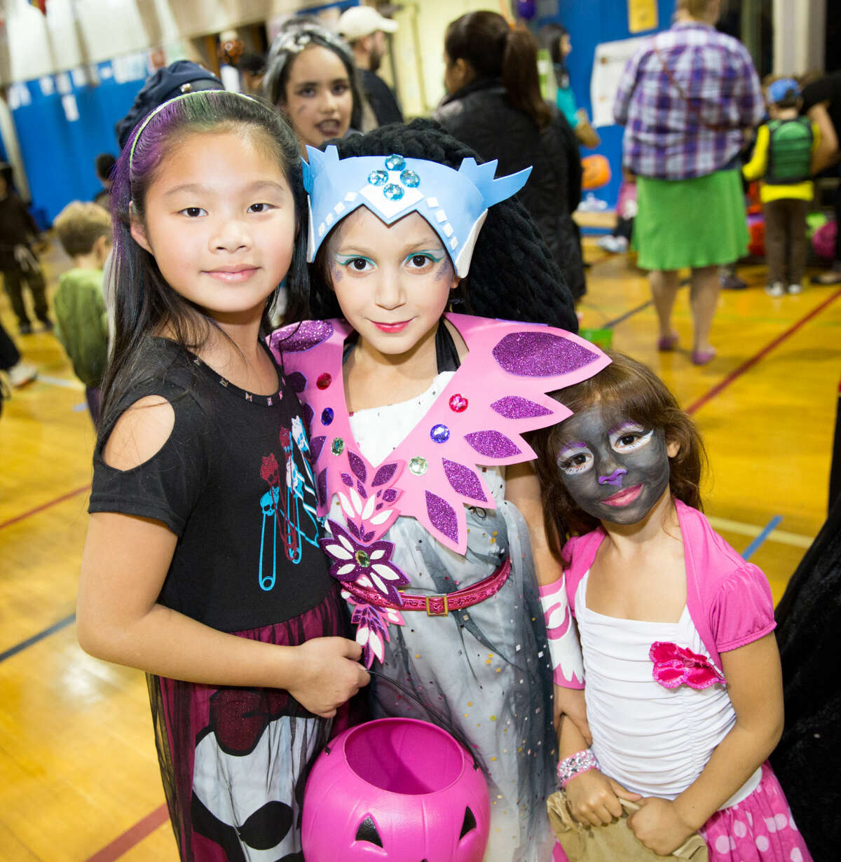 Hour photo/Chris Palermo Charlene Yang, Dasha Martin, and Zoya Martin show off their costumes at Silvermine Elementary's Halloween Spooktacular Thursday evening.