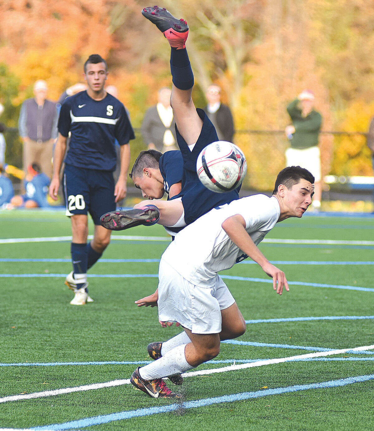 Hour photo/John Nash - Staples' Anton Mahr, center, gets upended by Darien's Sean Gallagher as the Wreckers' Joshua Berman (20) looks on during the second half of Thursday's FCIAC boys soccer playoff game in Darien. The Blue Wave won 2-0.
