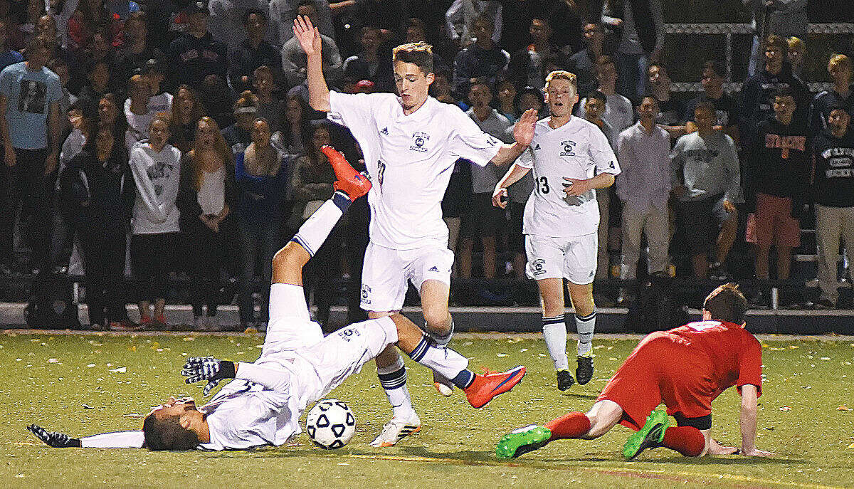 Hour photo/John Nash - Wilton's Harrison Allers, left, hits the turf after colliding with a Greenwich player as the Warriors' Daniel Jensen (23) and Nicholas Davatzes (13) look on during Thursday's FCIAC boys soccer quarterfinal at Kristine Lilly Field in Wilton. Greenwich the game, 2-1.