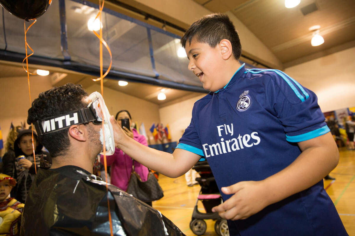 Hour photo/Chris Palermo Jose Partida serves a pie to the face at Silvermine Elementary's Halloween Spooktacular Thursday evening.