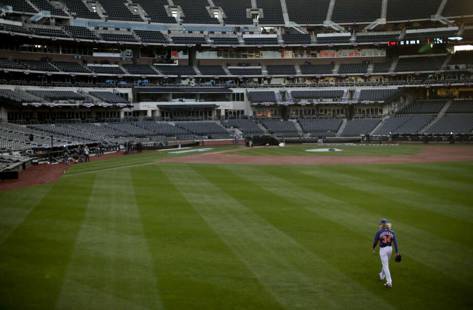 New York Mets pitcher Noah Syndergaard (34) walks across the field back to the clubhouse after working out in the bullpen, Thursday, Oct. 29, 2015, at CitiField in New York. The Mets host the Kansas City Royals in Game 3 of baseball's World Series on Friday. The Royals lead the best-of-seven games series 2-0. (AP Photo/Julie Jacobson)