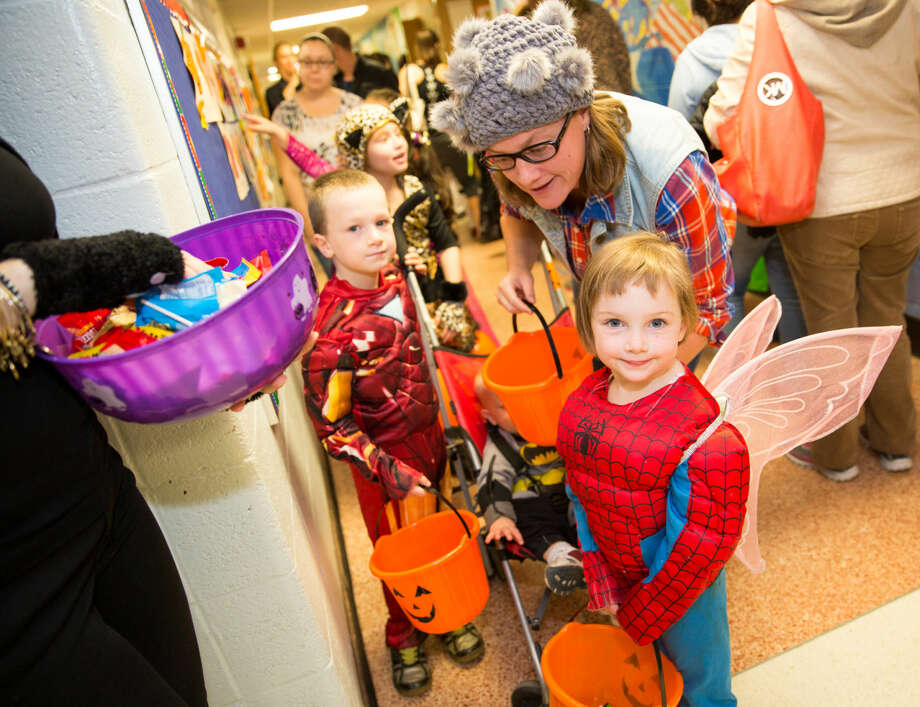 Hour photo/Chris Palermo Rachael Zazula, 4, trick or treats down the hall with her friends and family at Silvermine Elementary's Halloween Spooktacular Thursday evening.
