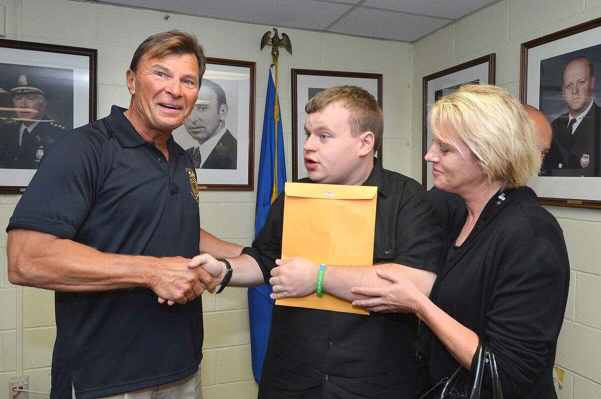 Hour Photo/Alex von Kleydorff Stamford Police Sgt. Paul Guzda and Patrick Kogut shake on it as he holds tightly on to an envelope of donated money with Patricks mom Irena, during a press conference at Police Headquarters