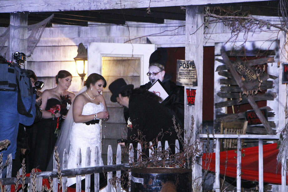 "In this photo provided by Spooky World Presents Nightmare New England, Melissa Cote and Tom Cowen, who both work at Spooky World Presents Nightmare New England in Litchfield, N.H., were married the night of Monday, Oct. 26, 2015, in front of the attraction's haunted house. During the ceremony, the justice of the peace encouraged them to ""haunt and howl at the moon together as long as you shall live,"" and ""to have and to hold from this night on, in madness and in haunting fun."" (Spooky World Presents Nightmare New England via AP)"