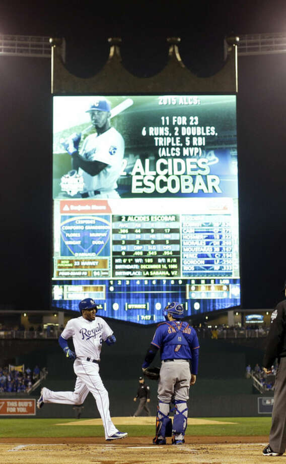 Kansas City Royals' Alcides Escobar, left, celebrates as he scores past New York Mets catcher Travis d'Arnaud on a inside-the-park home run during the first inning of Game 1 of the Major League Baseball World Series Tuesday, Oct. 27, 2015, in Kansas City, Mo. (AP Photo/Matt Slocum)