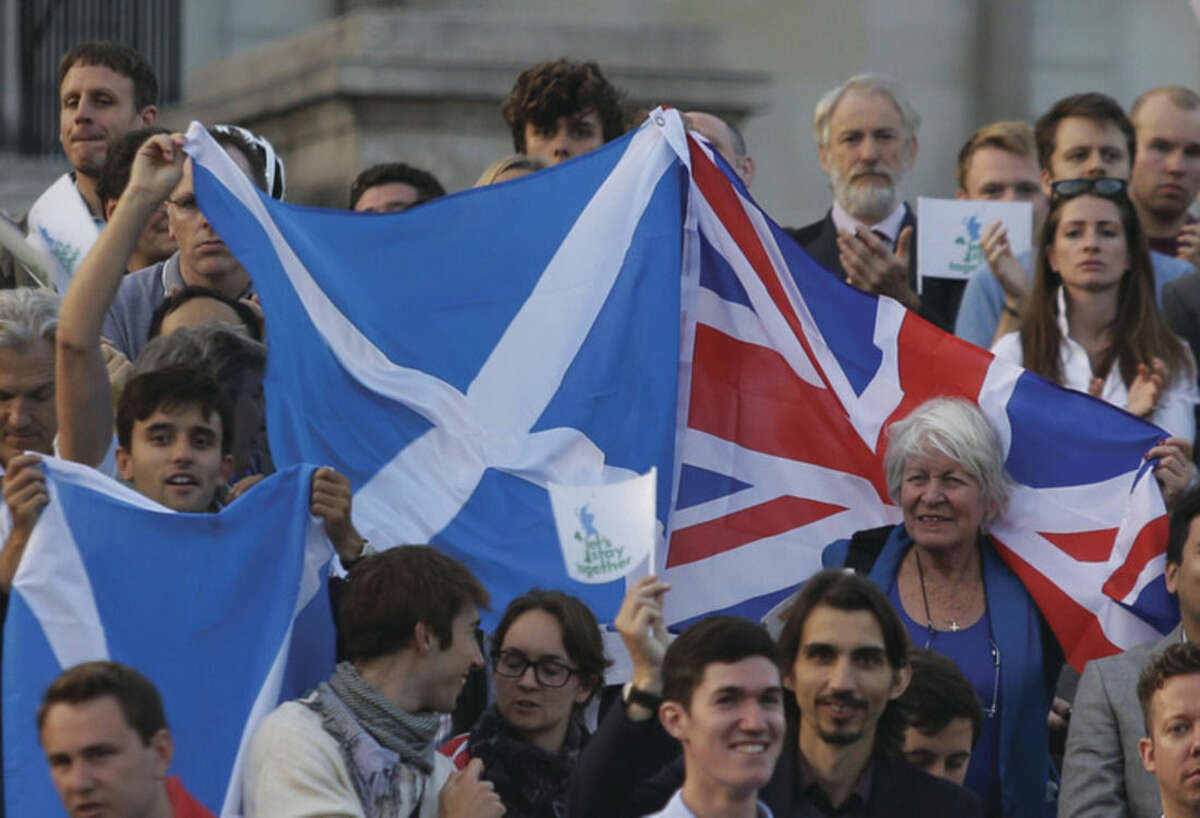 """AP photo/Lefteris Pitarakis Supporters wave British and Scottish flags at a pro-union rally rally at Trafalgar square in central London, Monday. Hundreds of people, supporters of the """"Lets Stay Together"""" campaign, gathered ahead of a referendum on whether Scotland should be an independent country. The voting will take place in Scotland on Thursday."""