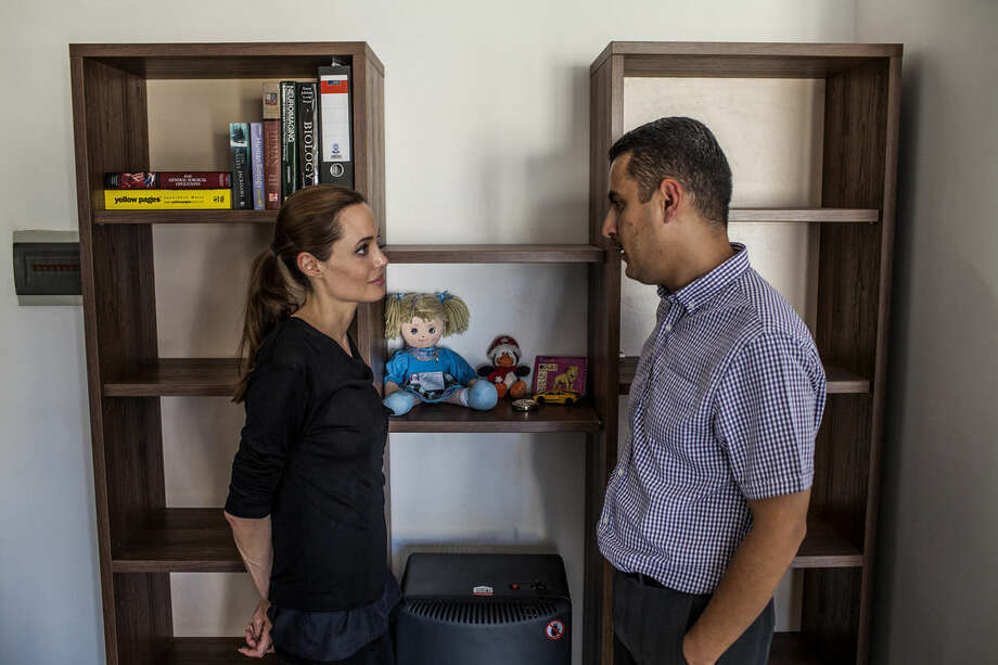 In this image made available from the UNHCR on Monday Sept. 15, 2014 United Nations High Commissioner for Refugees Special Envoy, Angelina Jolie, visits Dr. Ayman Mustafa, a Syrian refugee, at his apartment in Valetta, Malta on Saturday, Sept. 13, 2014. On October 11, 2013 a boat on which he, his wife and daughter boarded to seek refuge, capsized. His wife and daughter drowned. Since the start of 2014, more than 2,500 asylum seekers have perished trying to cross the Mediterranean.. (AP Photo/Pete Muller/Prime for UNHCR)