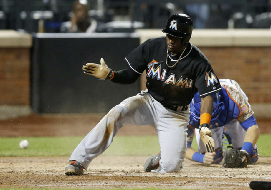 The ball rolls away from New York Mets catcher Travis d'Arnaud, right, as Miami Marlins Adeiny Hechavarria reacts after scoring on Jordany Valdespin's seventh-inning, two-run, single off New York Mets starting pitcher Jacob deGrom in a baseball game in New York, Monday, Sept. 15, 2014. (AP Photo/Kathy Willens)