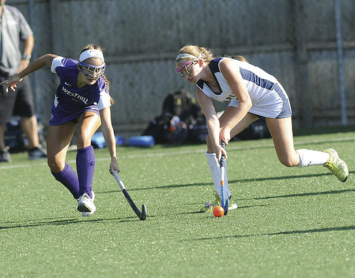 Hour photo/Matthew Vinci Staples' Jamie Tanzer, right, stick handles as Westhill's Emma Garsiulo defends during Monday's game.