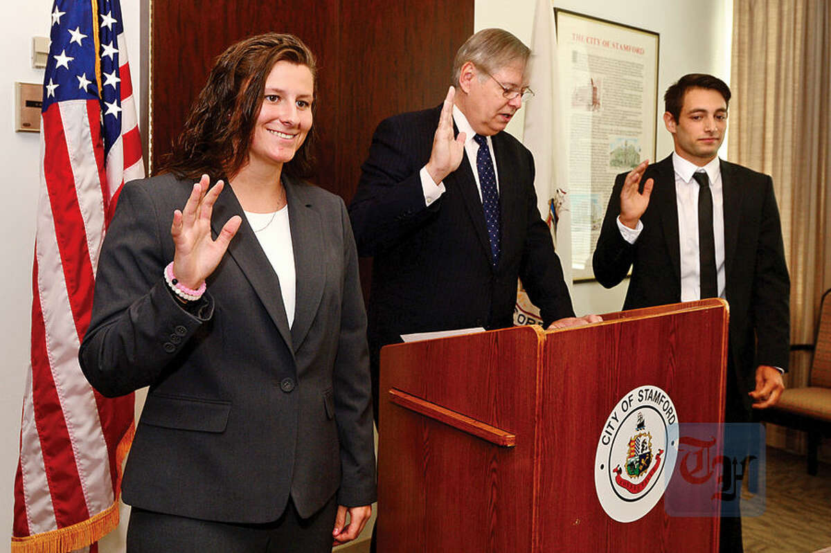 Stamford police recruits Lindsey Yanicky and John MCafferty are adminstered their oaths by Mayor David Martin during a swearing-in Ccremony for the new officers at the Stamford Governement Center on Thursday.