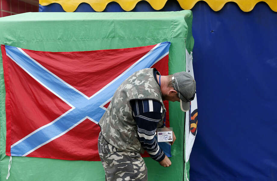 A Pro-Russian rebel arranges a flag of the self-proclaimed Federal State of Novorossiya in the town of Donetsk, eastern Ukraine, Tuesday, Sept. 16, 2014. The city council in Donetsk says three people have been killed and five wounded in shelling overnight in the city in eastern Ukraine. The casualties come as Ukraine's parliament plans to review a bill that would give greater autonomy to the eastern regions of Donetsk and Luhansk, where fighting between separatists and Kiev's forces has claimed at least 3,000 civilian lives. (AP Photo/Darko Vojinovic)