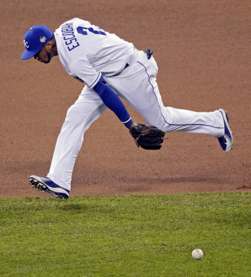 Kansas City Royals shortstop Alcides Escobar can't get a glove on a single by New York Mets' Yoenis Cespedes during the sixth inning of Game 1 of the Major League Baseball World Series Tuesday, Oct. 27, 2015, in Kansas City, Mo. (AP Photo/Charlie Riedel)
