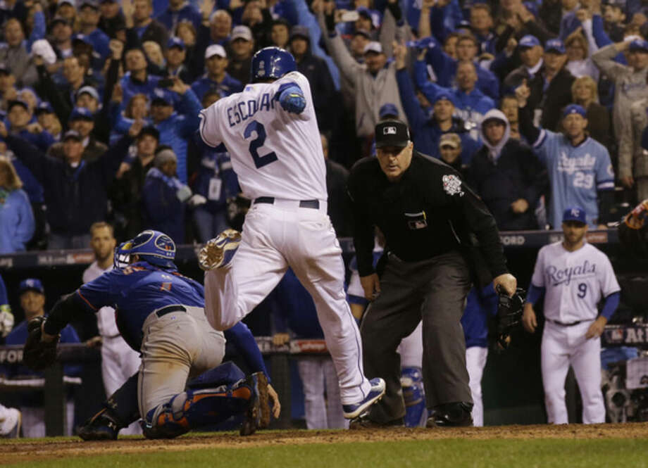Kansas City Royals' Alcides Escobar (2) scores on a sacrifice fly by Eric Hosmer during the 14th inning of Game 1 of the Major League Baseball World Series against the New York Mets Wednesday, Oct. 28, 2015, in Kansas City, Mo. (AP Photo/Matt Slocum)