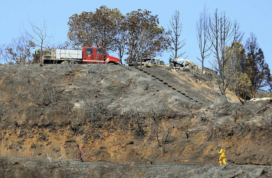 Damage lines the Black Bart Trail in Redwood Valley, Calif., Monday, Sept. 15, 2014. The wildfire is one of dozens to recently rip through the state, which has been rendered tinder-dry by three years of drought according to The Press Democrat. (AP Photo/The Press Democrat, Kent Porter)