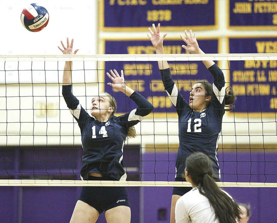 Hour photo/Chris PalermoWilton's Claire McCullough, left, and Carly Lovallo jump for the block against Westhill Wednesday evening. No results of this game were made available to The Hour.