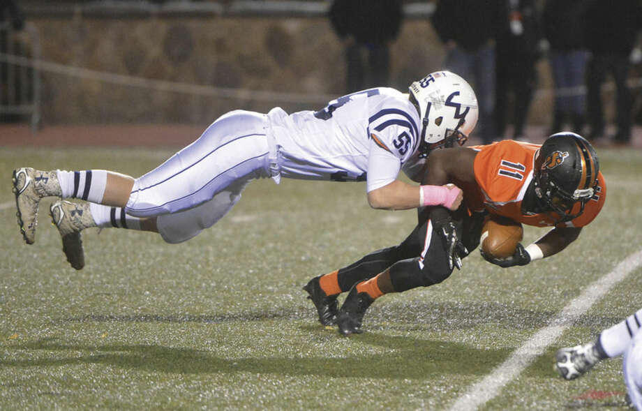 Photo by Alex von KleydorffStamford's Chris Desir, right, gets tackled by Wilton's Steffen Nobles during last Friday's game at Boyle Stadium in Stamford. Wilton won the game 30-27 in overtime.