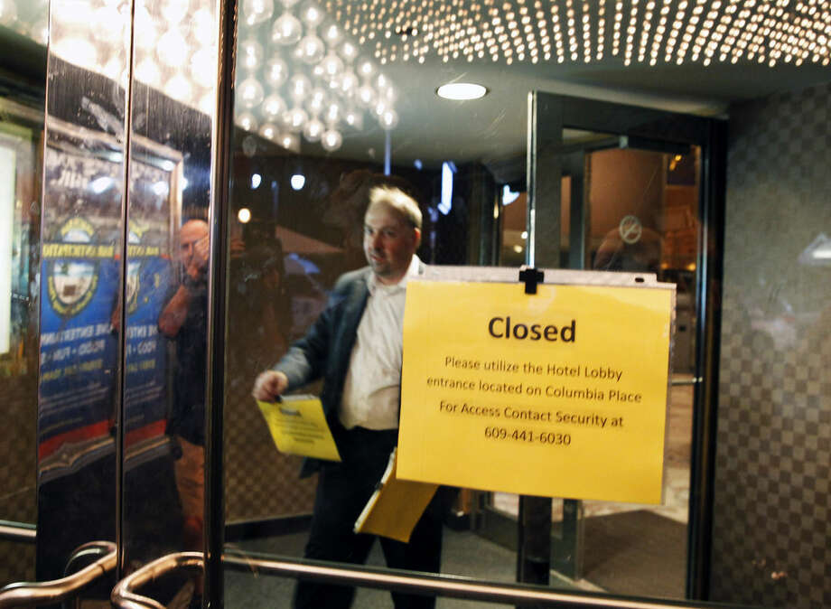 A worker posts closed signs on the lobby doors at Trump Plaza Hotel & Casino early Tuesday, Sept. 16, 2014, in Atlantic City, N.J. in Atlantic City, N.J. The hotel and casino closed its doors early Tuesday, the fourth Atlantic City casino to go belly-up so far this year. (AP Photo/Mel Evans)