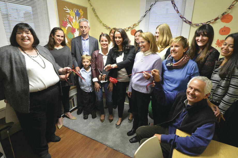 Hour photo/Alex von KleydorffThe Junior League of Stamford Norwalk help cut the ribbon for the Open Door Shelters Family Resource Center Wednesday.