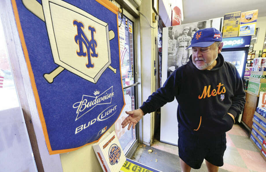 Hour photo/Erik Trautmann Bob Macedo looks over some of his many New York Mets artifacts in his Broad River liquor store, which has become like a sports museum.