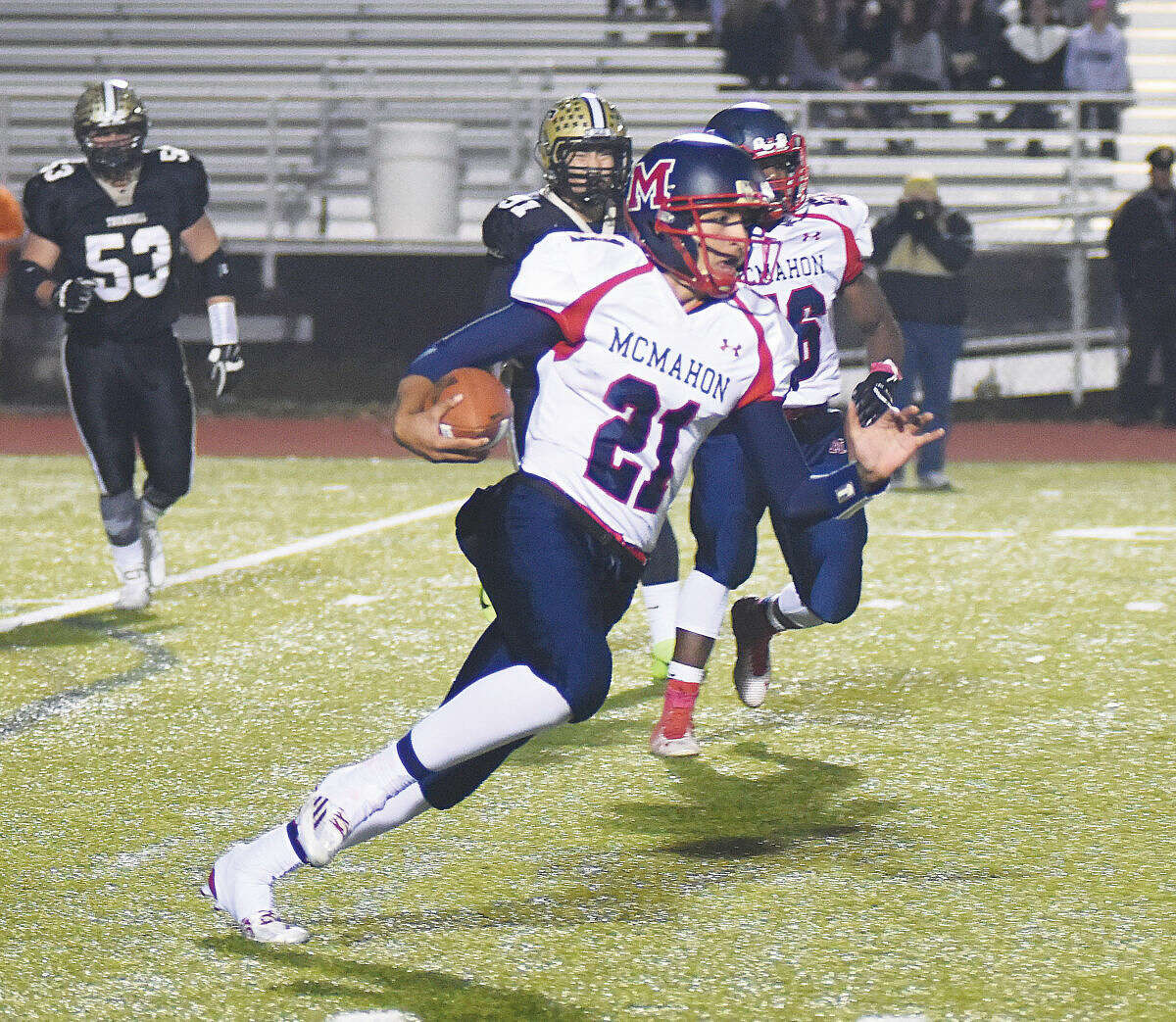McMahon quarterback Chris Druin looks for running room after getting chased from the pocket during Friday night's game at McDougal Stadium in Trumbull. The host Eagles won, 33-17. (Hour photo/John Nash)