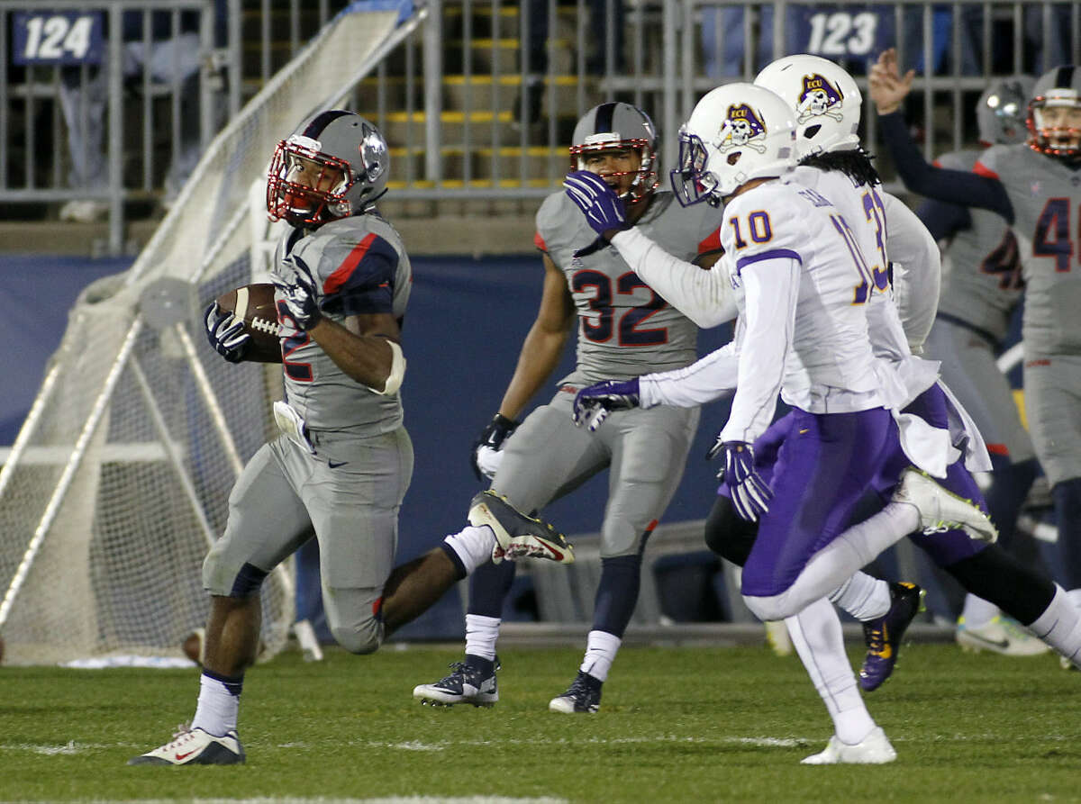 Connecticut running back Arkeel Newsome, left, runs for a 90-yard touchdown as East Carolina defensive back Rocco Scarfone (10) and defensive back Domonique Lennon, right, pursue during the third quarter of an NCAA college football game, Friday, Oct. 30, 2015, in East Hartford, Conn. (AP Photo/Stew Milne)