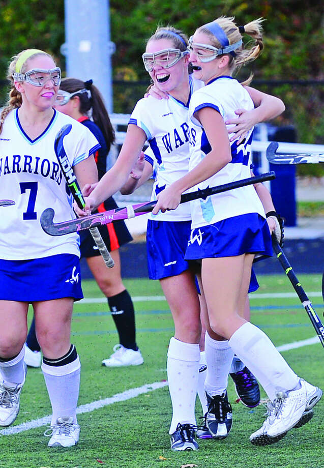 Hour photo / Erik Trautmann Wilton's Caroline Ferro and Bridgette Ward celebrate with Maddy Duffy after her goal against Ridgefield in their quarter final game in Wilton Friday.