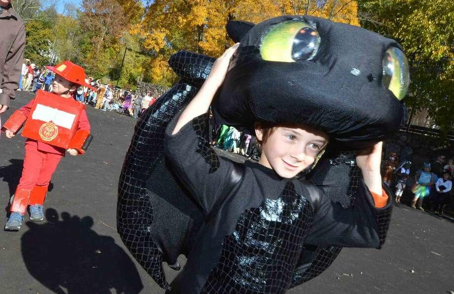 Hour Photo/Alex von Kleydorff Kindergartener Jason Kurtzman holds on at 'Toothless' from How to Train your Dragon during the Rowayton Elementary School's Halloween parade