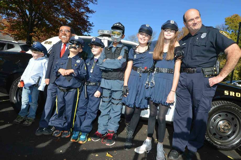 Hour Photo/Alex von Kleydorff Norwalk police School Resource Officer Cornell Abruzzini poses with the President and 'fellow' officers during the Rowayton Elementary School's Halloween parade