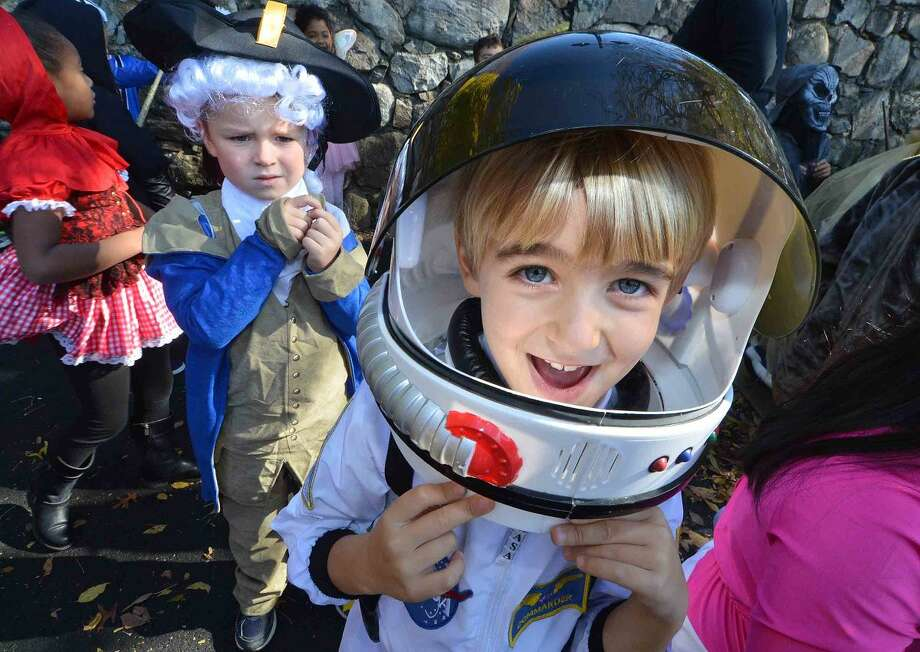 Hour Photo/Alex von Kleydorff 1st grader Henry Carr buckles his helmet ready for the parade during the Rowayton Elementary School's Halloween parade