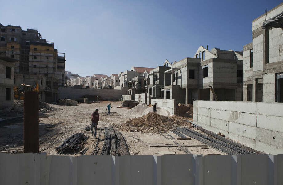 Palestinians laborers work at a construction site in the Jewish West Bank settlement of Maale Adumim, near Jerusalem. Tuesday, Sept. 16, 2014. Israel's settler population in the West Bank increased by 2 percent in the first half of the year, an advocacy group announced Tuesday, signaling robust growth in the settlements even while Israel was conducting peace talks with the Palestinians. The new figures drew criticism from the Palestinians, who seek the West Bank as part of a future state. The Palestinians and most of the international community consider Israeli construction there to be illegal or illegitimate. (AP Photo/Dan Balilty)