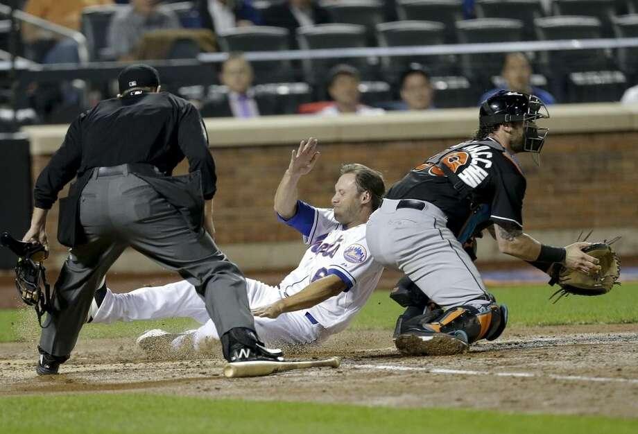 New York Mets Matt den Dekker (6) slides past Miami Marlins catcher Jarrod Saltalamacchia to score on a Ruben Tejada double during the fourth inning of a baseball game Tuesday, Sept. 16, 2014, in New York. (AP Photo/Frank Franklin II)