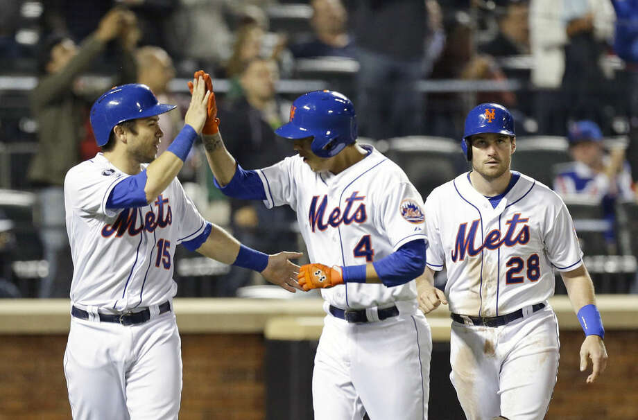 New York Mets' Travis d'Arnaud (15) and Daniel Murphy (28) celebrate with Wilmer Flores (4) after they scored on a three run home run during the fifth inning of a baseball game against the Miami Marlins Tuesday, Sept. 16, 2014, in New York. (AP Photo/Frank Franklin II)