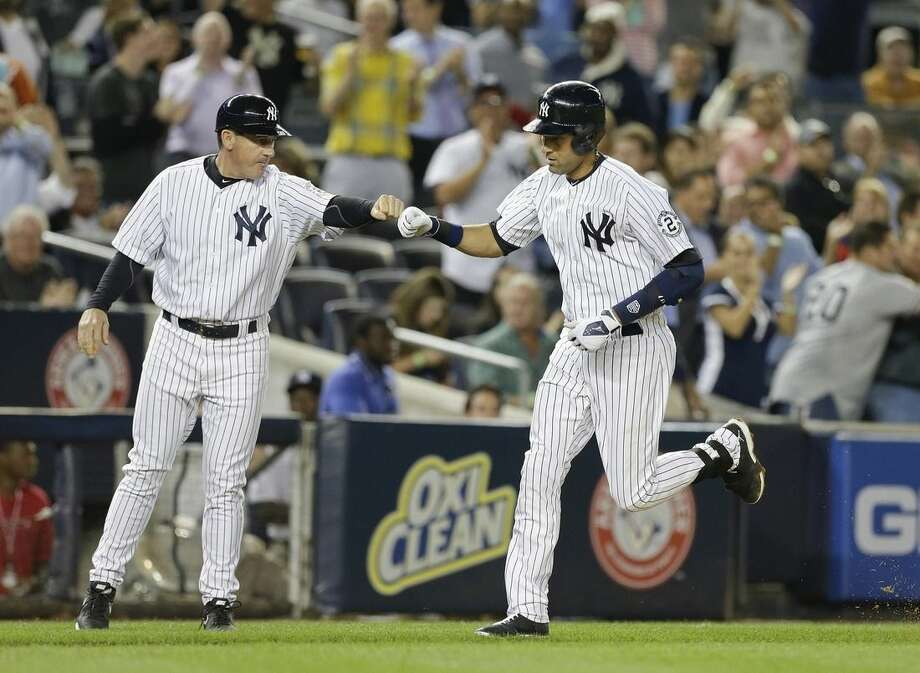 New York Yankees' Derek Jeter bumps fists with third base coach Rob Thomson on his way to home plate after hitting a home run during the sixth inning of a baseball game against the Toronto Blue Jays Thursday, Sept. 18, 2014, in New York. (AP Photo/Frank Franklin II)