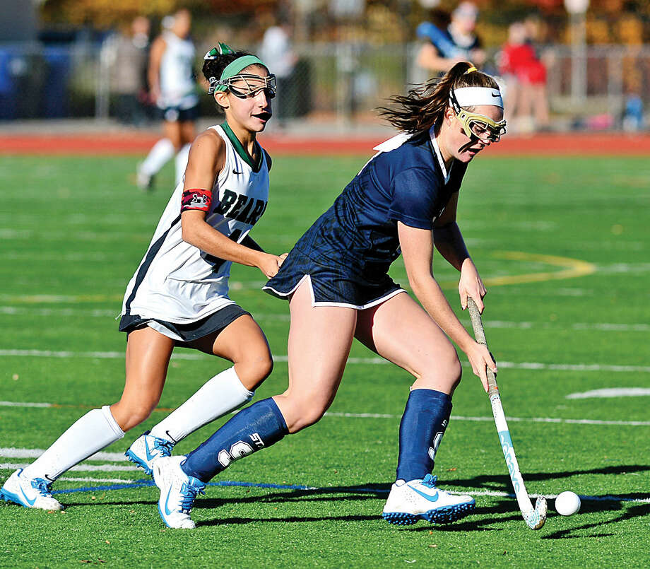 Hour photo / Erik Trautmann Staples High School Field Hockey player Colleen Bannon takes the ball past Norwalk's Marissa Mastrianni in their quarter final game in Norwalk Saturday.