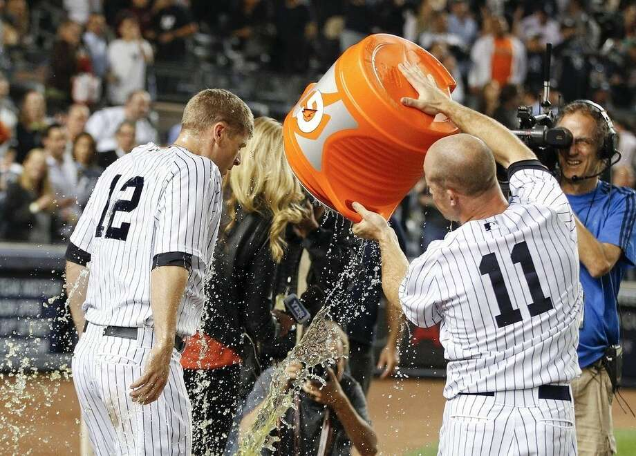New York Yankees' Brett Gardner (11) douses teammate Chase Headley (12) after Headley drove in the baseball game-winning run during the ninth inning against the Toronto Blue Jays, Thursday, Sept. 18, 2014, in New York. (AP Photo/Frank Franklin II)