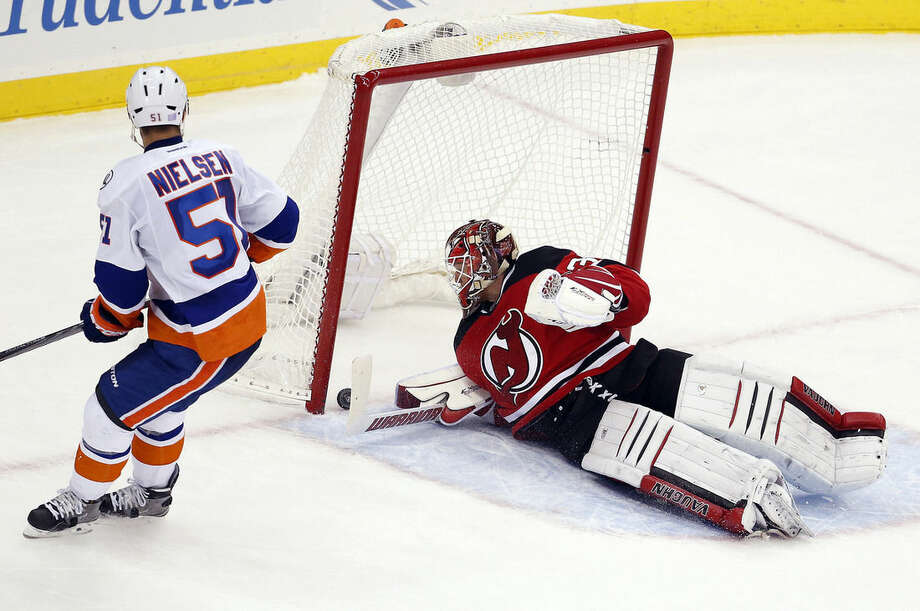 New Jersey Devils goalie Cory Schneider, right, is unable to stop a shot by New York Islanders center Frans Nielsen (51), of Denmark, during a shootout in an NHL hockey game, Saturday, Oct. 31, 2015, in Newark, N.J. The Devils won 3-2 in a shootout. (AP Photo/Julio Cortez)