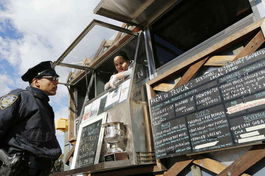 """Snowday staffer Marivette Alicea, 25, right, discusses the food truck's """"gourmet lumberjack"""" menu with a New York city police officer as he decides what to order during Smorgasburg at Brooklyn's Grand Army Plaza, Sunday, Oct. 18, 2015, in New York. The truck is part of the nonprofit Drive Train program that prepares formerly incarcerated youth to re-enter the job market. They're taught to cook, plus hospitality, money management and even emotional development. (AP Photo/Kathy Willens)"""
