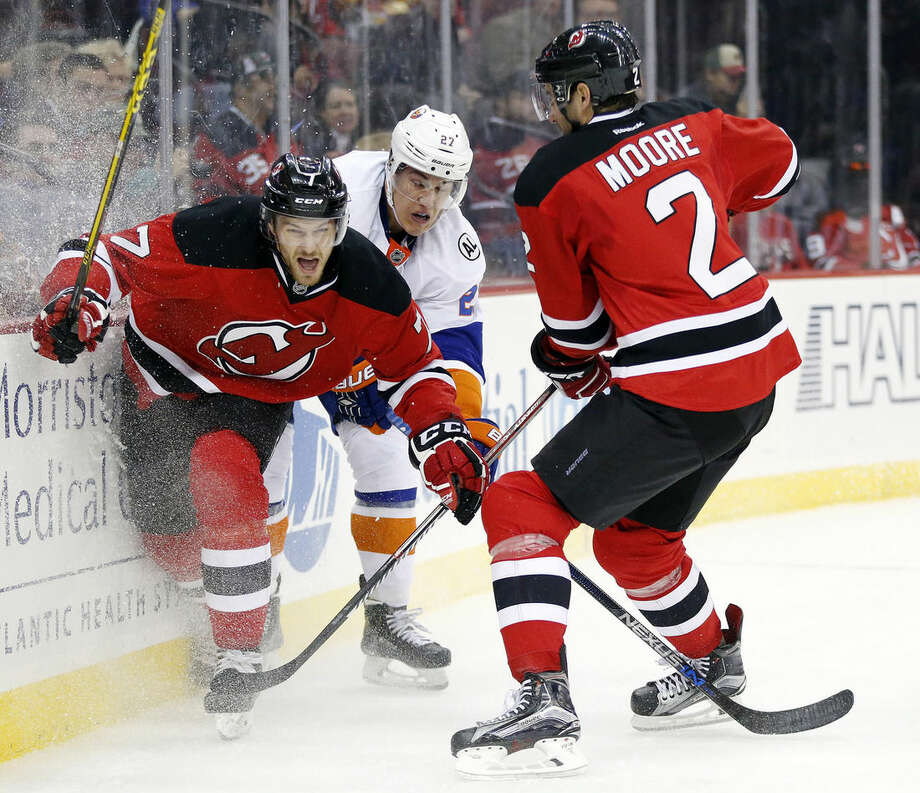 New York Islanders center Anders Lee, center, skates against New Jersey Devils defenseman Jon Merrill (7) and defenseman John Moore (2) during the first period of an NHL hockey game, Saturday, Oct. 31, 2015, in Newark, N.J. (AP Photo/Julio Cortez)