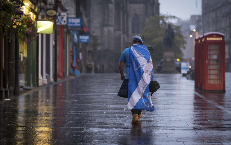 A lone YES campaign supporter walks down a street in Edinburgh after the result of the Scottish independence referendum, Scotland, Friday, Sept. 19, 2014. Scottish voters have rejected independence and decided that Scotland will remain part of the United Kingdom. The result announced early Friday was the one favored by Britain's political leaders, who had campaigned hard in recent weeks to convince Scottish voters to stay. It dashed many Scots' hopes of breaking free and building their own nation. (AP Photo/PA, Stefan Rousseau) UNITED KINGDOM OUT, NO SALES, NO ARCHIVE