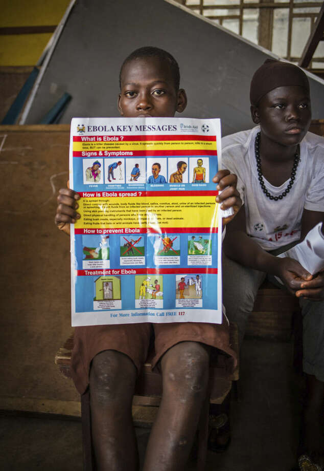 A child holds up a poster, as he and others are educated on how to prevent and identify the Ebola virus in their communities by charity worker's from GOAL Ireland humanitarian agency, at Freetown, Sierra Leone, Thursday, Sept. 18, 2014. Shoppers crowded streets and markets in Sierra Leone's capital on Thursday stocking up for a three-day shutdown that authorities will hope will slow the spread of the Ebola outbreak that is accelerating across West Africa. (AP Photo/ Michael Duff)