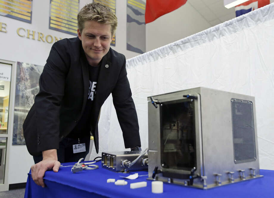 Brad Kohlenberg, a business development engineer with Made In Space, looks over a 3-D printer identical to the one that will be transported to the International Space Station aboard the Falcon 9 SpaceX rocket at the Kennedy Space Center in Cape Canaveral, Fla., Friday, Sept. 19, 2014. NASA is sending a 3-D printer to the International Space Station in hopes that astronauts will be able to one day fix their spacecraft by cranking out spare parts on the spot. (AP Photo/John Raoux)