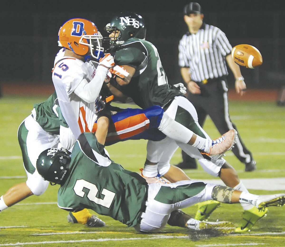 Hour photo/John Nash Danbury's Tysheen McCrea (15) has the ball dislodged on a vicious hit by Norwalk's Eric Cohens (right) as Bear teammates Harrison Hefferan (2) and Brendan Brown, rear, join on the tackle. Norwalk recovered the fumble, but lost the game 14-6.